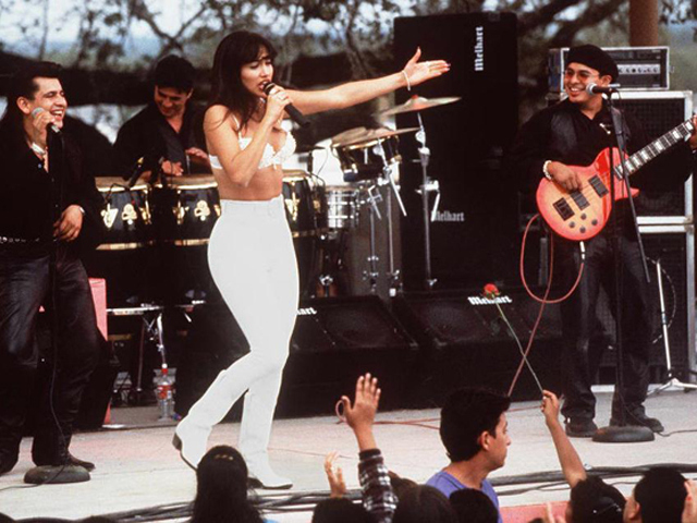 "HOLLYWOOD, CA - MARCH 23:  Actress Jennifer Lopez, who plays Selena in the movie ""Selena,"" performs with her band in one of the scenes from the movie.  ""Selena"" is about the tejano singer who is murdered by her fan club president.  (Photo credit should read RICCO TORRES/AFP/Getty Images)"